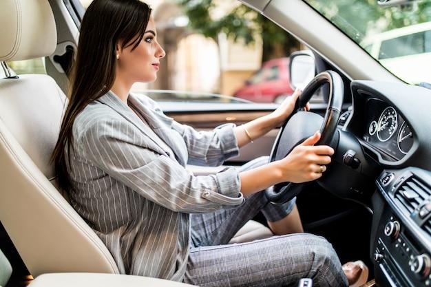 Rijden door de stad. jonge aantrekkelijke vrouw glimlacht en kijkt recht tijdens het besturen van een auto Gratis Foto