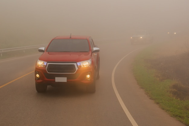 Rijdende auto's in de mistberg met koplampstralen in dichte mist. Premium Foto