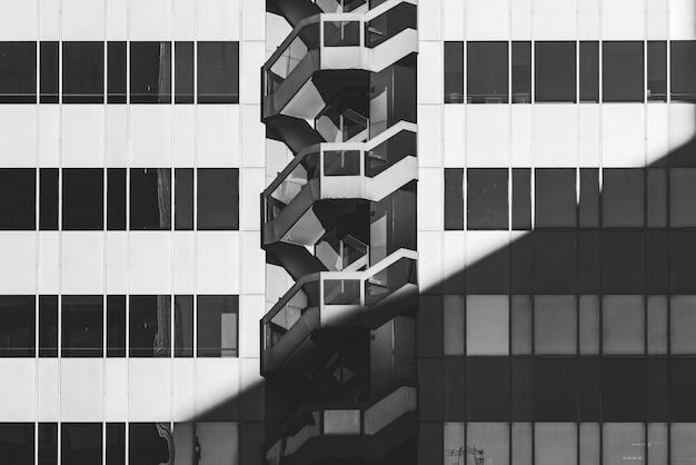 Rijen met glazen ramen en buitentrap van de gevel van een kantoorgebouw in zwart-wit Premium Foto
