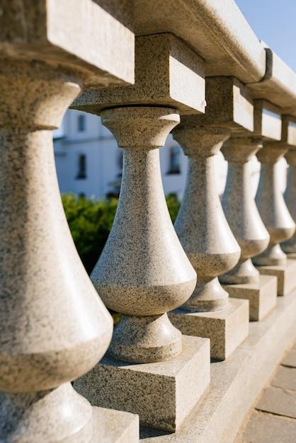 Rijen van granieten balusters. het gebouw is ingericht in een klassieke stijl. Premium Foto