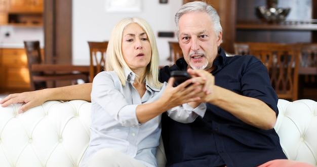 Rijp paar die voor afstandsbediening op een bank vechten Premium Foto