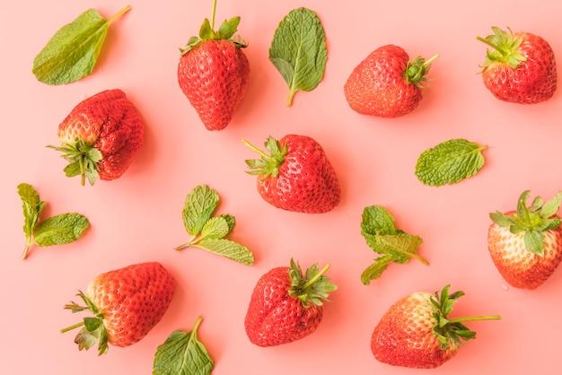 Rijpe aardbeien en muntblaadjes op achtergrond Gratis Foto