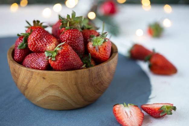 Rijpe aardbeien in een houten kom op een witte tafel Premium Foto
