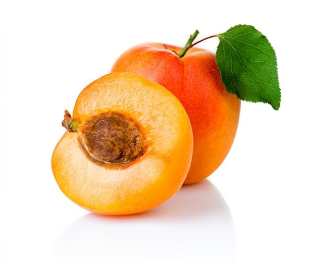 Rijpe abrikozenvruchten met met groen blad en geïsoleerde plak Premium Foto