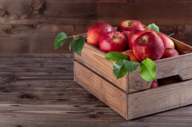 Rijpe appels met bladeren in houten mand op de rustieke tafel. Premium Foto