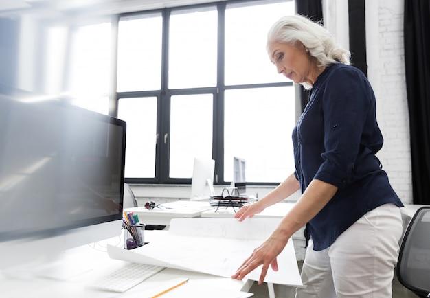 Rijpe bedrijfsvrouw die een grafiek analyseren die voor haar wordt gehouden Gratis Foto