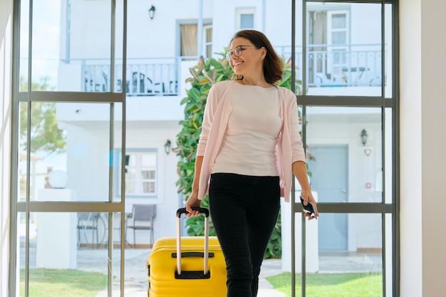 Rijpe bedrijfsvrouw in hotelbinnenland met koffer Premium Foto