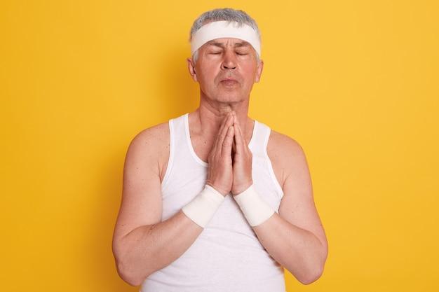 Rijpe blanke man met wit t-shirt en hoofdband, ogen gesloten, handen bij elkaar, biddend voor beter leven Gratis Foto
