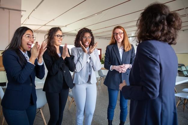 Rijpe collega die aan gelukkige jongere collega's spreekt Gratis Foto