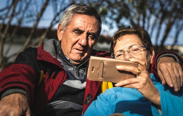 Rijpe die vrouw met smartphone door haar echtgenoot wordt omhelst terwijl allebei die in park zitten Premium Foto