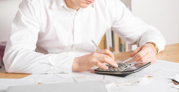 Rijpe eigenaar van kleine onderneming die financiële rekeningen van activiteiten berekent - ondernemer die laptop en calculator gebruikt om te werken en om financiële kosten van het opstarten van nieuwe bedrijven te berekenen en te analyseren Premium Foto