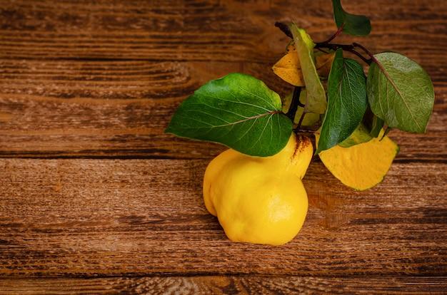 Rijpe gele kweepeer op houten rustieke achtergrond. kopieer ruimte. biologische seizoensfruit. Premium Foto