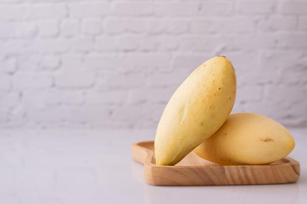 Rijpe gele mango's op wit bord. Premium Foto