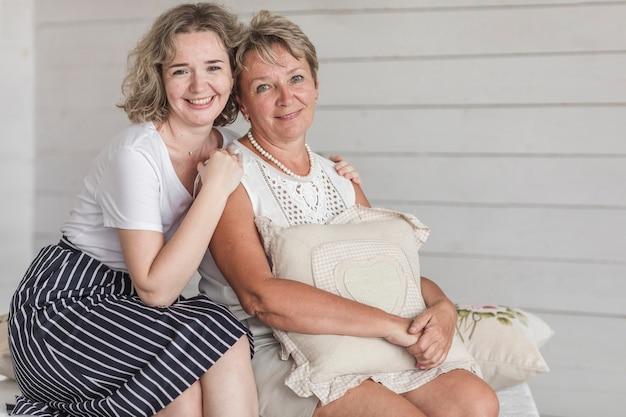 Rijpe glimlachende het kussenzitting van de moedergreep met haar mooie dochter Gratis Foto