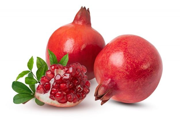 Rijpe granaatappelfruiten met bladeren op de witte achtergrond. met uitknippad. Premium Foto