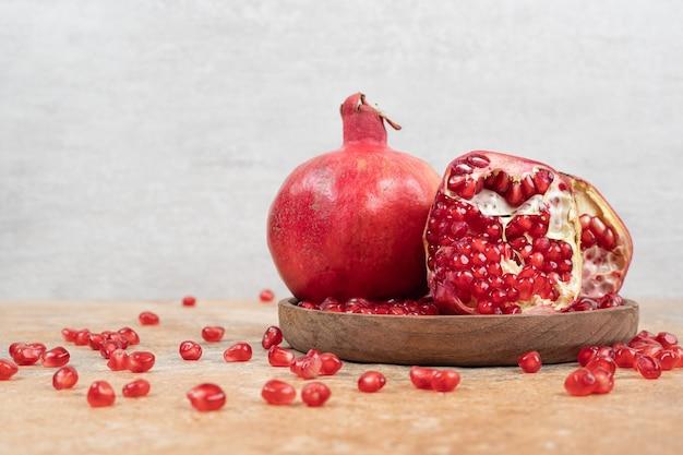 Rijpe granaatappels en zaden op houten plaat. Gratis Foto