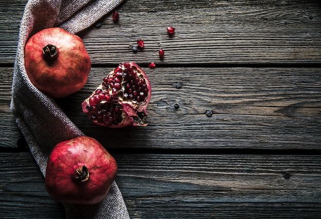Rijpe granaatappels, servet en tafelmes op witte houten achtergrond Premium Foto