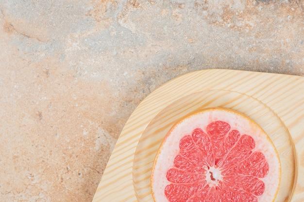 Rijpe grapefruitplak op houten plaat. hoge kwaliteit foto Gratis Foto