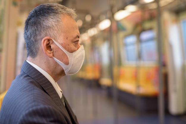 Rijpe japanse zakenman die masker draagt en met afstand binnen de trein zit Premium Foto