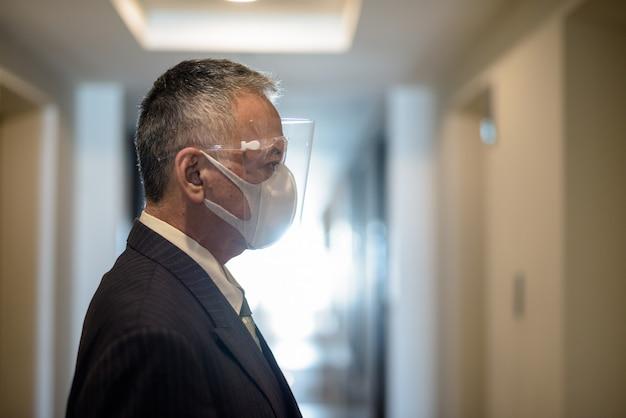 Rijpe japanse zakenman die met masker en gezichtsschild op de lift wacht Premium Foto