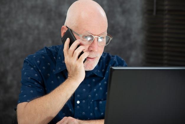 Rijpe man met een baard en een blauw shirt op kantoor Premium Foto