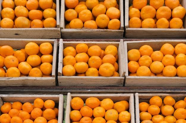 Rijpe mandarijnen in houten kisten staan op een rij. Premium Foto
