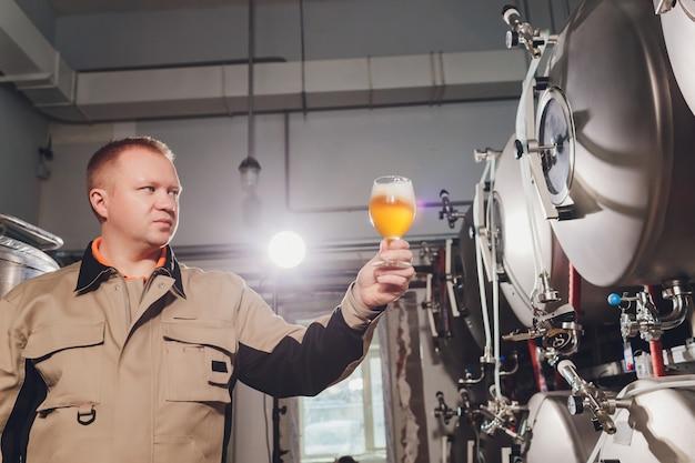 Rijpe mens die de kwaliteit van ambachtbier onderzoekt bij brouwerij. inspecteur die bij alcohol productiefabriek werkt die bier controleert. mens die in distilleerderij kwaliteitscontrole van bier van het vat controleert. Premium Foto