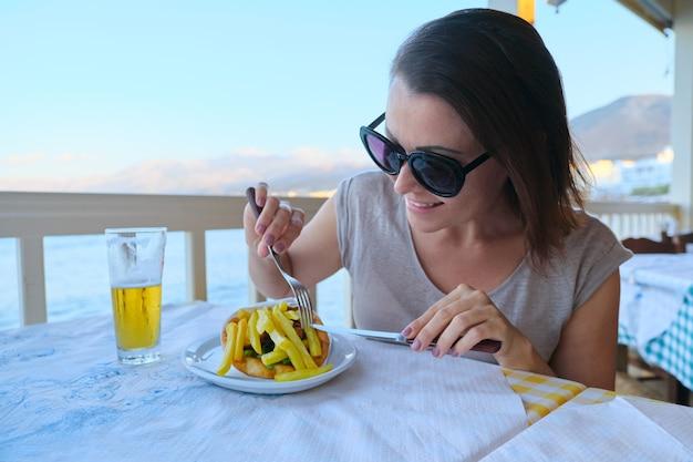 Rijpe mooie vrouw die diner heeft bij badplaatskoffie Premium Foto