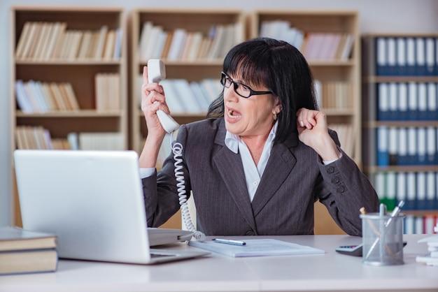 Rijpe onderneemster die in het bureau werkt Premium Foto