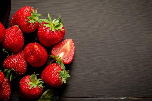 Rijpe rode aardbeien op zwarte houten tafel Premium Foto