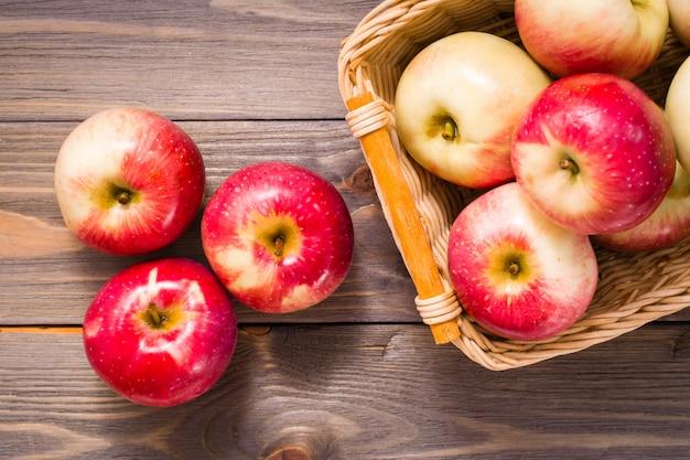 Rijpe rode appels en mand met appels op een houten tafel. copyspace Premium Foto