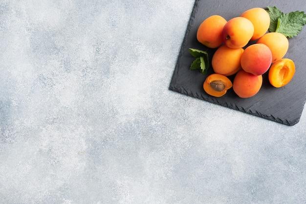 Rijpe sappige abrikozen met muntblaadjes Premium Foto
