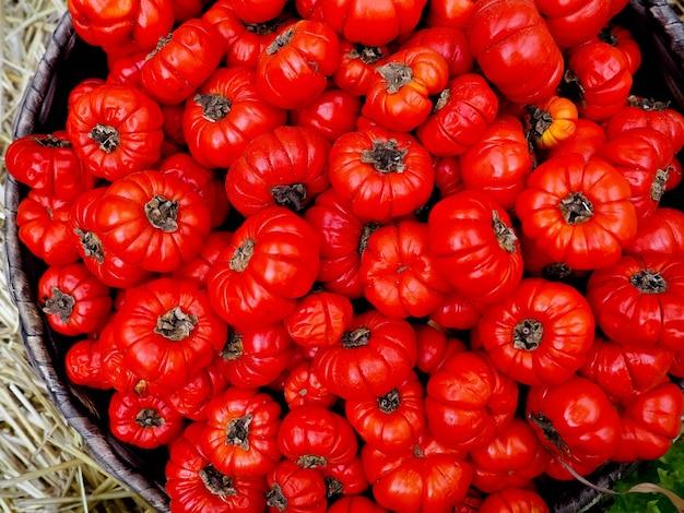 Rijpe tomaten in een mand op een aard. plat leggen Premium Foto