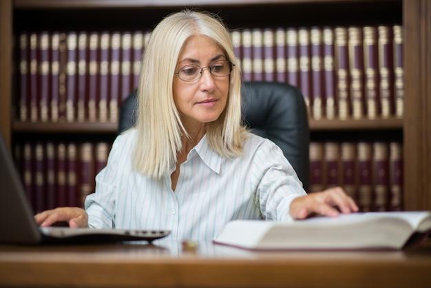 Rijpe vrouw die haar laptop computer met behulp van terwijl het lezen van een boek Premium Foto