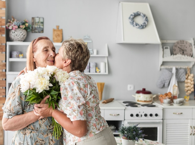 Rijpe vrouw die haar moeder kussen die wit bloemboeket thuis houden Gratis Foto
