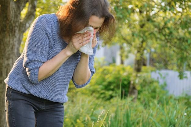 Rijpe vrouw die in zakdoek niest, allergie voor stuifmeel, verkoudheid Premium Foto