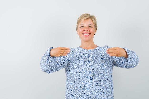 Rijpe vrouw in jurk gebaren met handen plat gehouden en op zoek gelukkig Gratis Foto