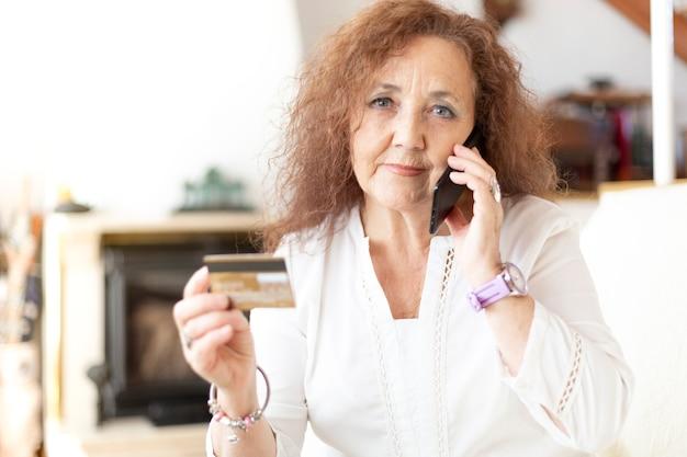 Rijpe vrouw praten aan de telefoon vanuit haar huis terwijl ze een creditcard in haar hand houdt. Premium Foto