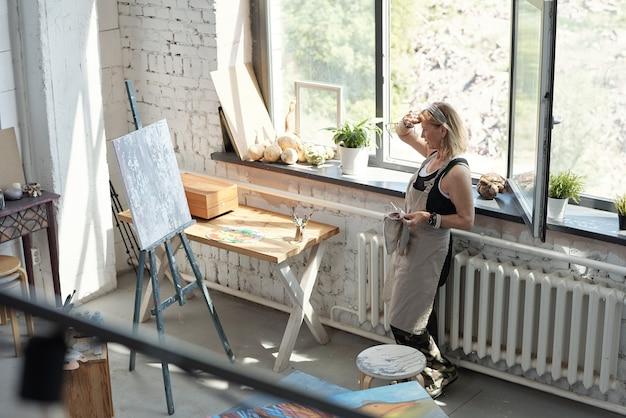 Rijpe vrouwelijke artiest in schort moe na het schilderen van zweet van het voorhoofd afvegen en kijken naar abstract beeld Premium Foto
