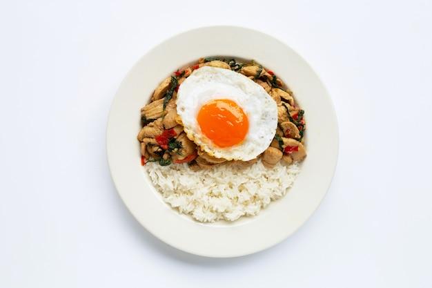 Rijst afgedekt met geroerbakte kip en heilige basilicum, gebakken ei Premium Foto