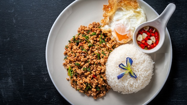 Rijst afgedekt met geroerbakte varkensvlees en basilicum op houten. thais eten Premium Foto