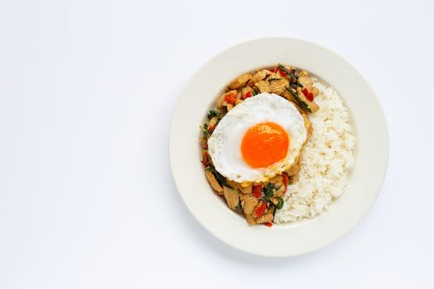 Rijst gegarneerd met gewokte kip en heilige basilicum, gebakken ei Premium Foto