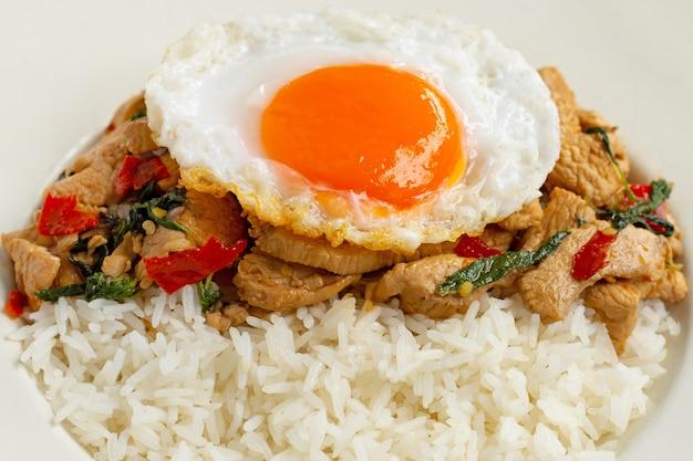 Rijst gegarneerd met gewokte kip en heilige basilicum Premium Foto