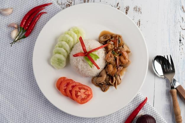 Rijst gegarneerd met roergebakken basilicum met inktvis en garnalen Gratis Foto
