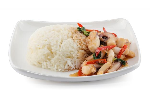 Rijst gegarneerd met roergebakken inktvis en basilicum geïsoleerd op een witte achtergrond Premium Foto