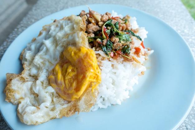 Rijst gegarneerd met roergebakken varkensgehakt en basilicum met gebakken ei. Premium Foto