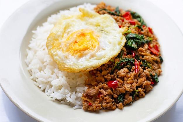 Rijst gegarneerd met roergebakken varkensvlees met basilicum en gebakken ei Premium Foto