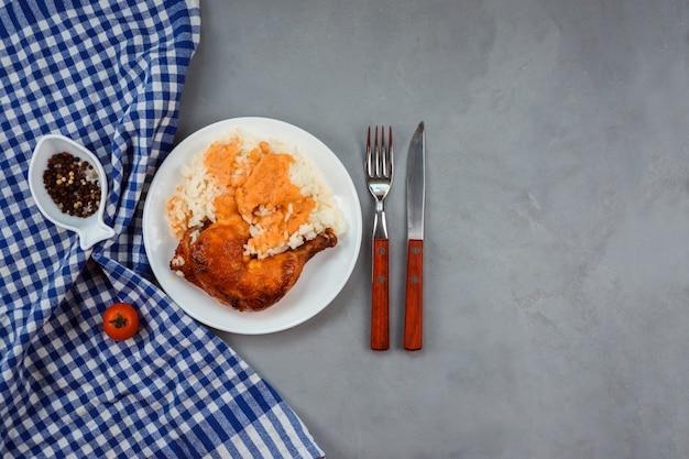 Rijst onder currysaus met gebakken kippenpoot geserveerd op de witte plaat. blauwe handdoek, peper in de visvormige kom, mes en vork versieren grijze achtergrond. Premium Foto