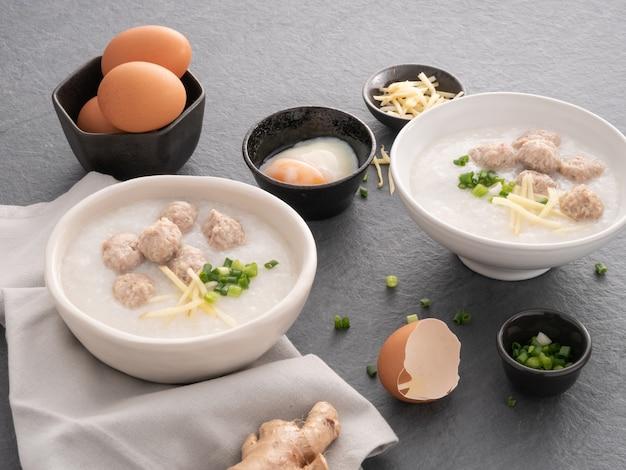 Rijstcongee met fijngehakt varkensvlees in witte kom. kom rijstepap met zacht gekookt ei. aziatisch ontbijt Premium Foto