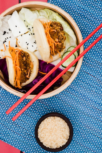 Rijstkorrelschaal met gua bao en salade in de bamboestoomboot op placemat Gratis Foto
